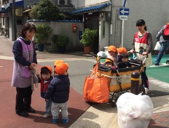 Маленьких детей воспитатели возят погулять на тележке...