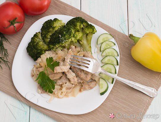 Бефстроганов из свинины с овощами на тарелке