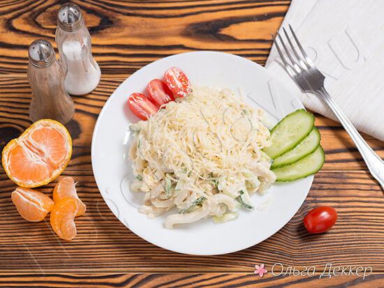 Салат из кальмаров с огурцом на тарелке