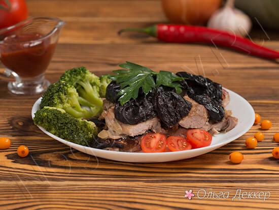 Свинина с черносливом на столе с овощами